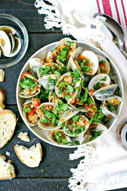 steamed clams topped with chopped parsley next to sliced bread