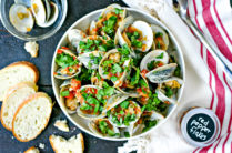white bowl of steamed clams in tomato sauce topped with lots of parsley