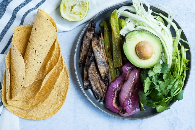 platter of cooked vegan taco filling with corn tortillas and fresh lime