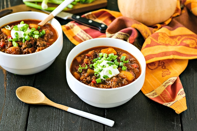 two bowls of butternut squash chili with wood spoons and an orange napkin