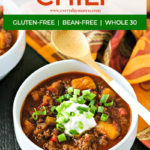 white bowl of butternut squash chili topped with scallions