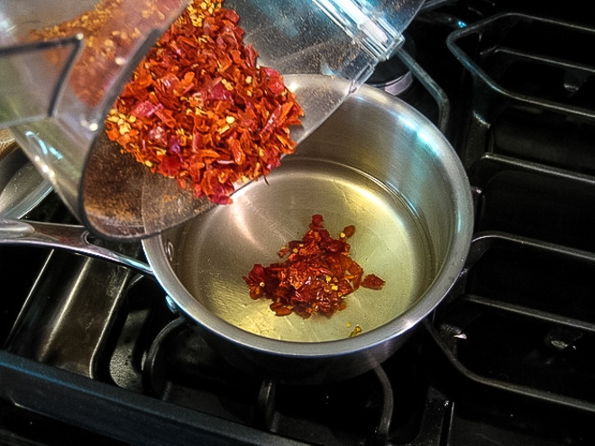 pouring chopped chili's into hot oil to make homemade chili oil