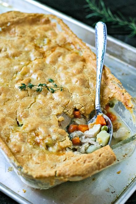 cooked paleo chicken pot pie on a baking sheet with a serving spoon