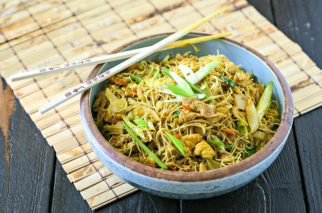 bowl of singapore rice noodles on a wood mat with chopsticks