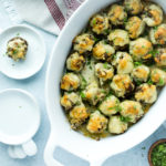 close up of baked stuffed mushrooms in a white baking dish