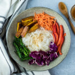 noodle bowl filled with cooked glass noodles, rainbow veggies and sesame dressing
