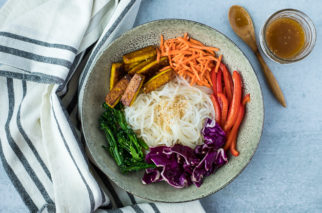 grey bowl with glass noodles and vegetables next to a striped linen