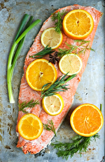 whole salmon fillet with sliced citrus and herbs on a baking sheet