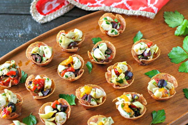 salami cups filled with antipasto on a wood serving tray