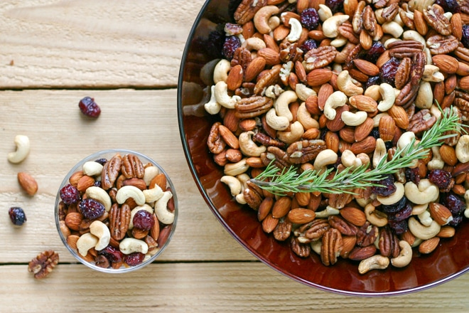 large bowl of mixed nuts topped with fresh rosemary