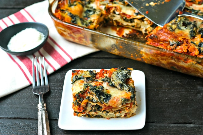 slice of vegetarian lasagna on a white plate in front of casserole dish