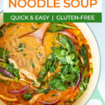 thai red curry noodle soup in a large pot topped with cilantro