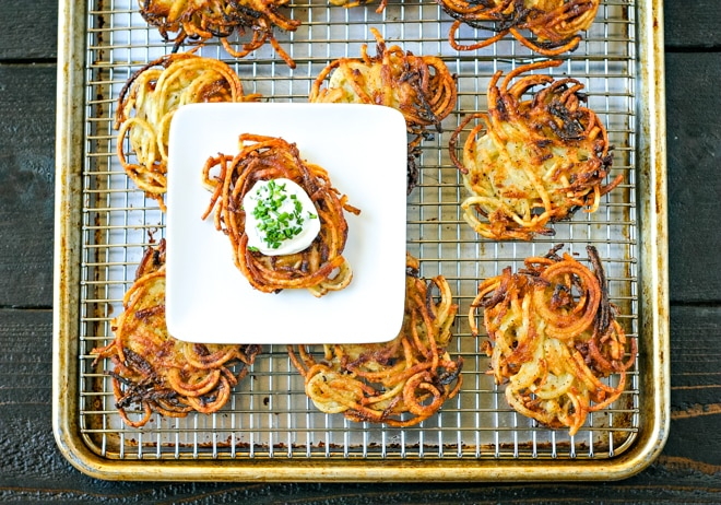 tray of potato latkes with white plate holding one latke topped with sourcream and chives