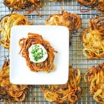 small white plate with potato latke topped with sour cream and chives