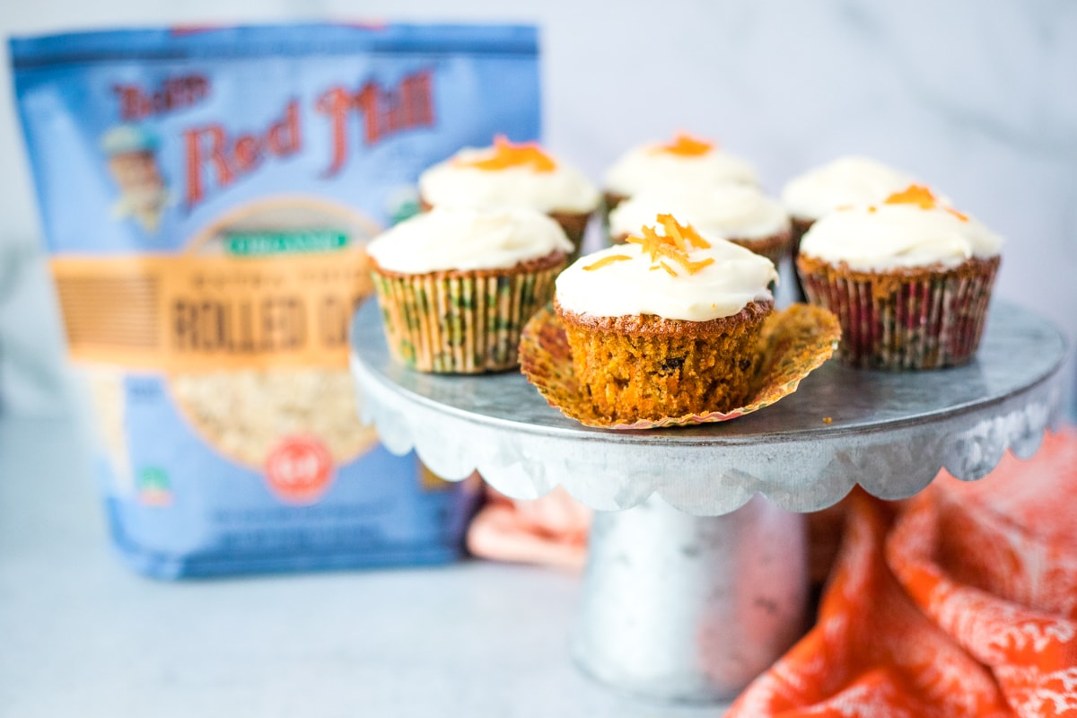 cake stand of carrot muffins with a bag of rolled oats in the background