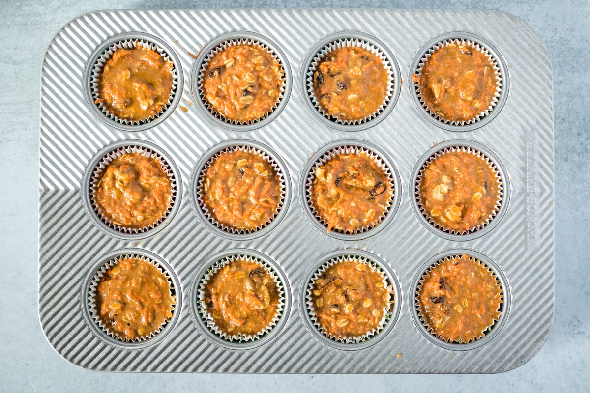 carrot muffin batter in a muffin pan ready to go into the oven
