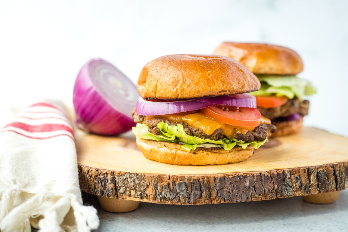 horseradish burgers with sliced onion on a wood cutting board