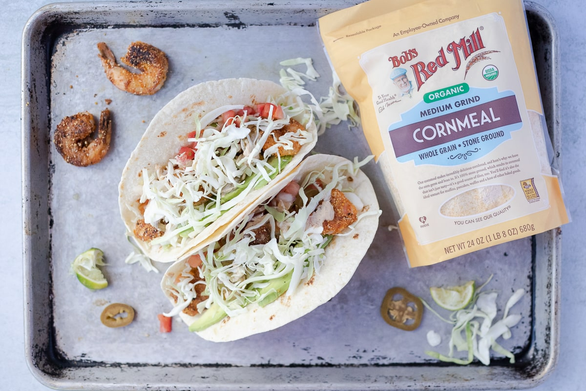 two shrimp tacos with all the toppings next to a bag of Bob's Red Mill cornmeal