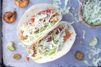 two crispy shrimp tacos with shredded cabbage
