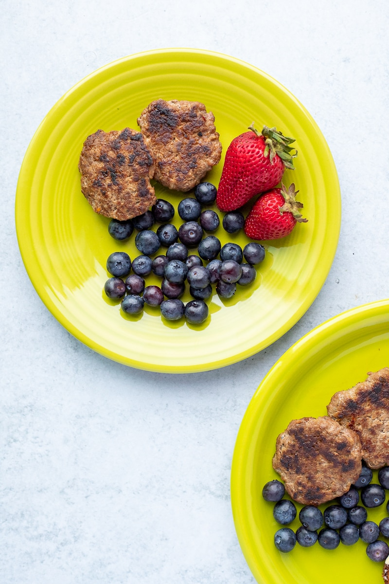 green plates with cooked breakfast sausage, blueberries and strawberries