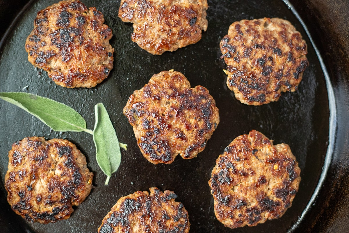 cast iron skillet with cooked breakfast sausage patties and fresh sage leaves