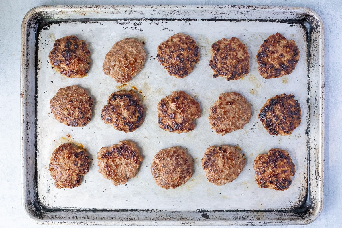 fully cooked breakfast sausage patties on a baking sheet