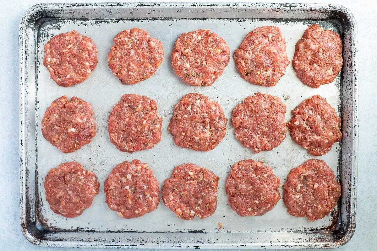 uncooked breakfast sausage patties on a baking sheet