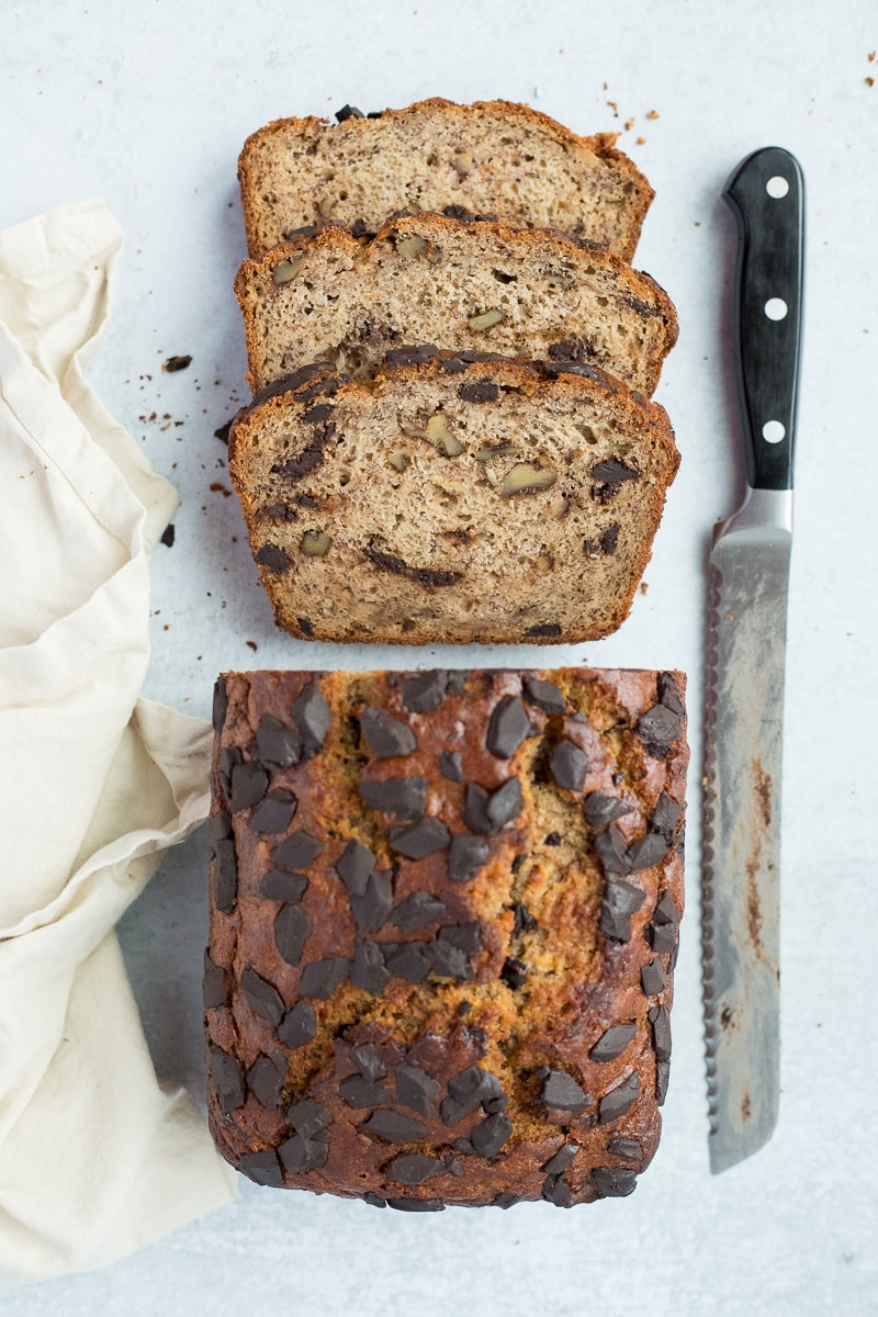 sliced banana bread with a serrated knife and linen