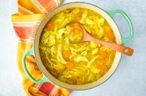 large pot of turmeric chicken soup with ladle in it ready to serve