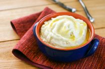 blue ceramic bowl filled with mashed cauliflower topped with melted butter