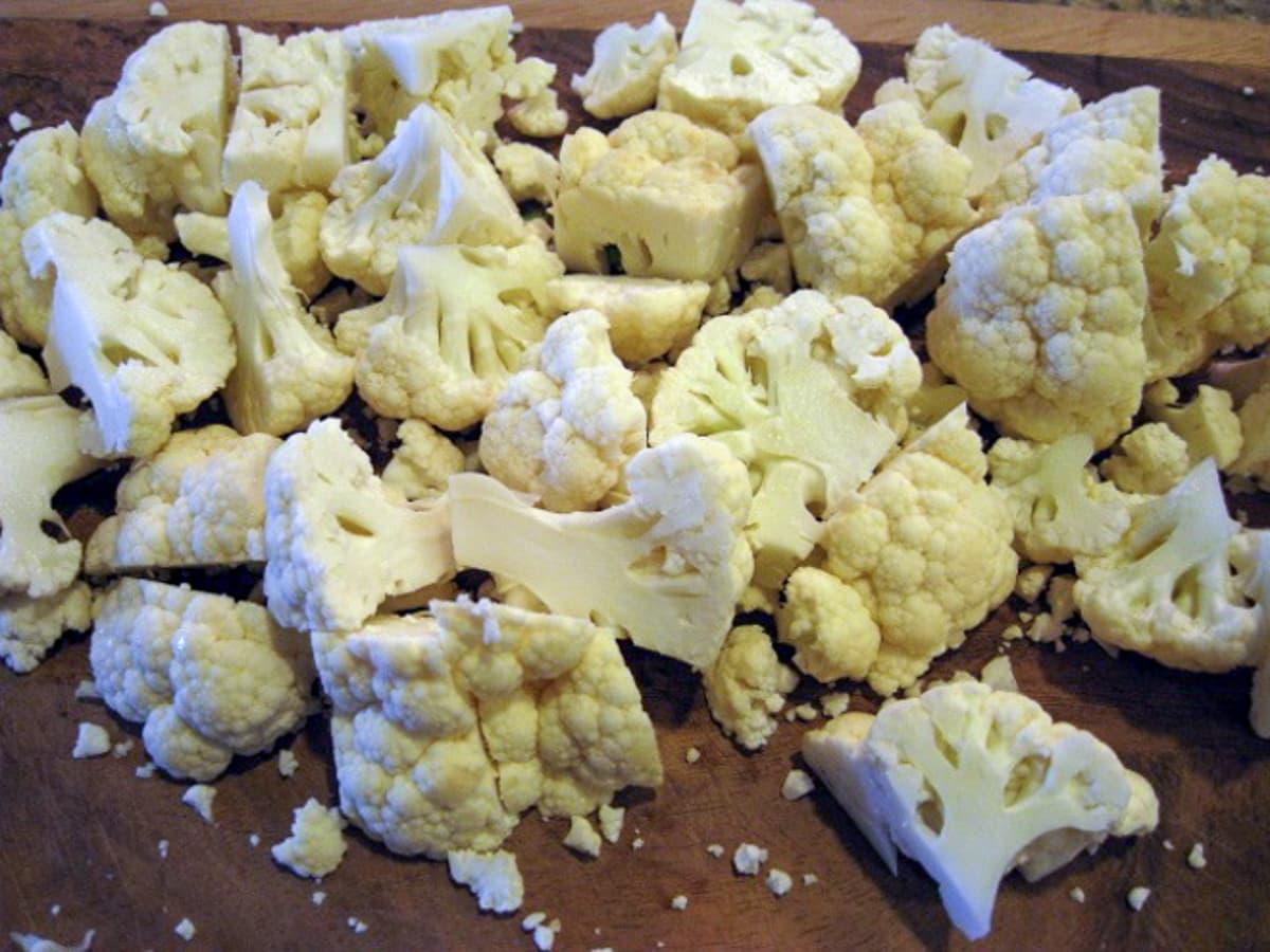 cut up cauliflower on a wood board