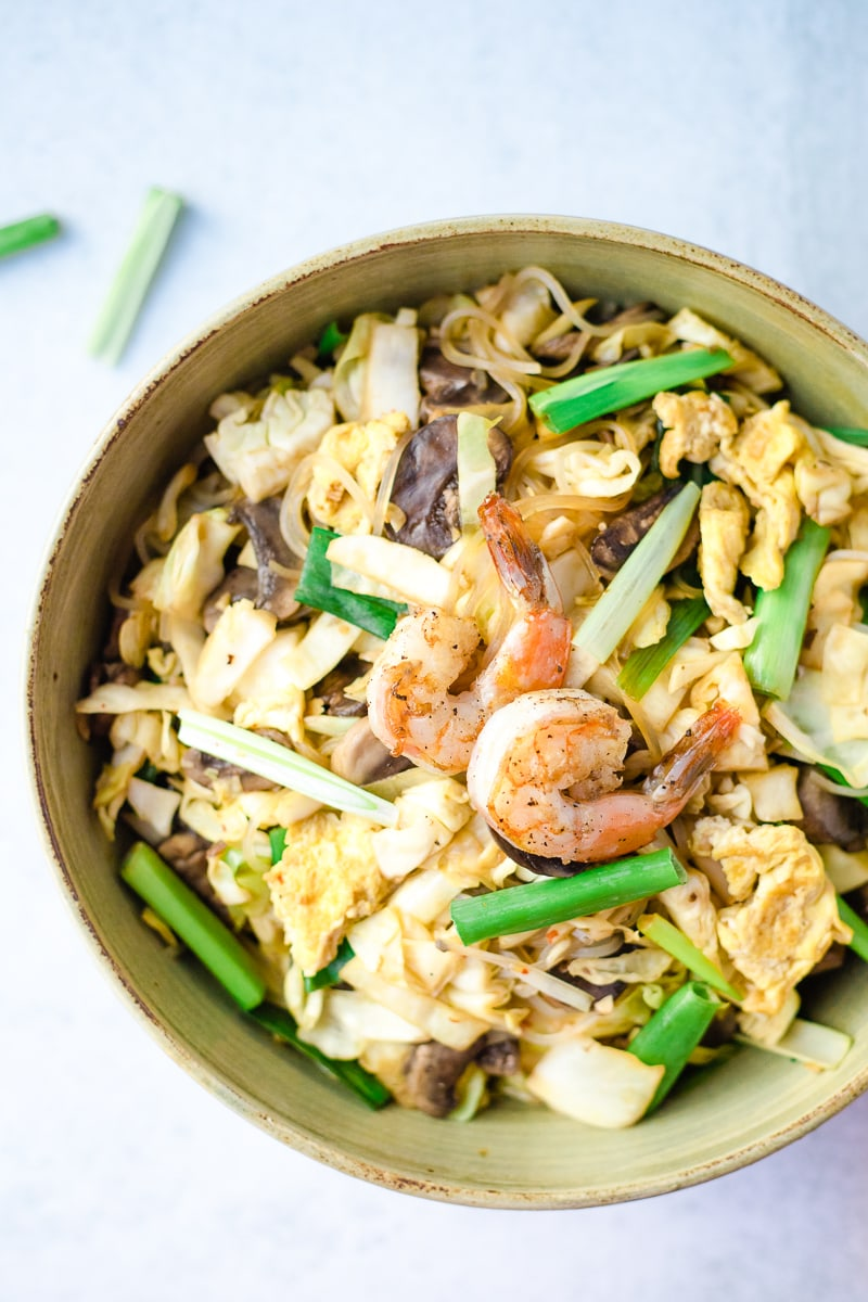 noodle stir fry topped with shrimp in a large ceramic bowl