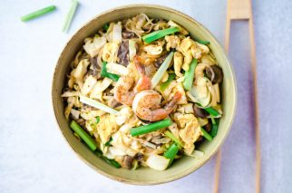 glass noodle stir fry with cabbage, mushrooms and scallions in a serving bowl