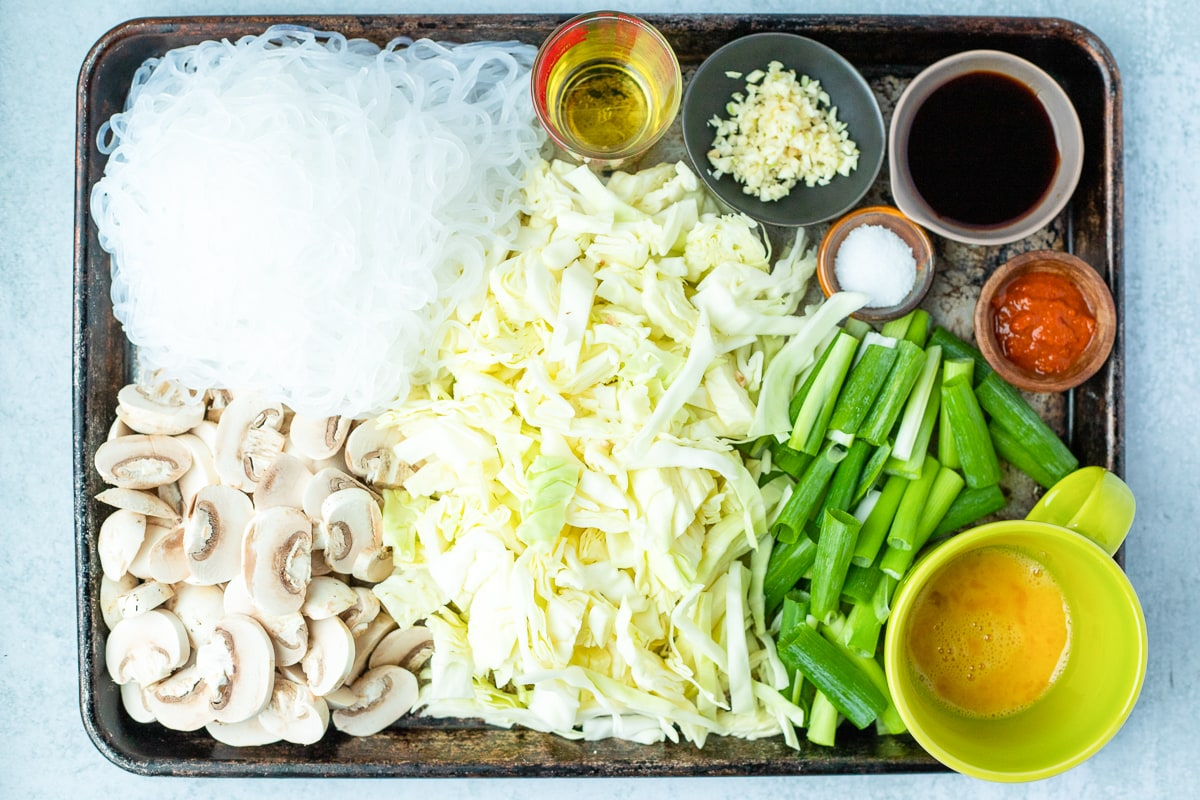 prepped and measured out ingredients for glass noodle stir fry on a baking sheet
