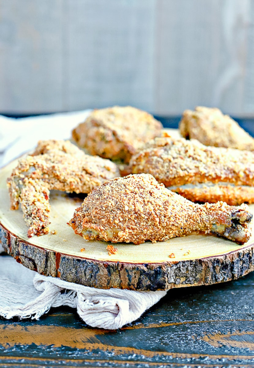 paleo fried chicken on a wood tray with a beige linen