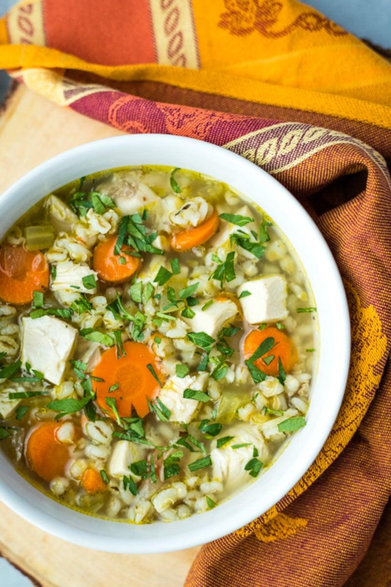 large bowl of turkey barley soup with festive orange linen