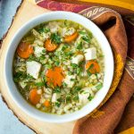 bowl of turkey barley soup topped with parsley