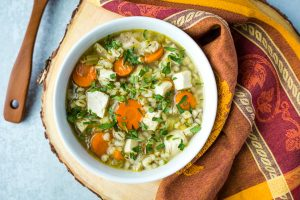white bowl of turkey barley soup with colorful autumn linen and wood spoon