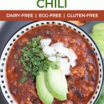 close up of bowl of chili with avocado, cilantro and onion on top