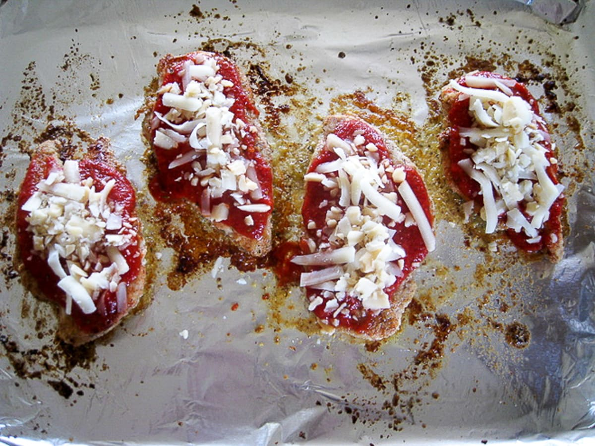 topping breaded chicken with sauce and mozzarella cheese on a baking sheet
