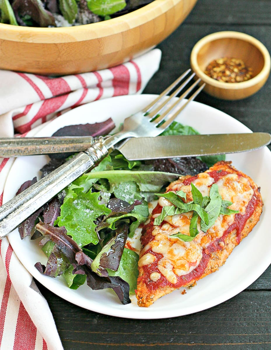 white dinner plate with cooked chicken parmesan and salad