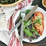 white plate with gluten-free chicken parmesan and salad
