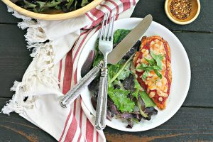 plate of gluten-free chicken parmesan with salad and knife and fork