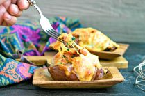 stuffed sweet potatoes on a wood dish topped with melted cheese