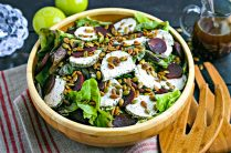 wood salad bowl with fall salad topped with goat cheese rounds and pumpkin seeds