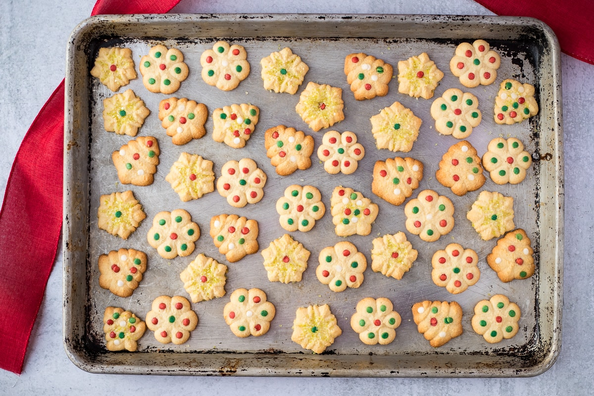 cookie sheet with decorated butter cookies and red ribbon