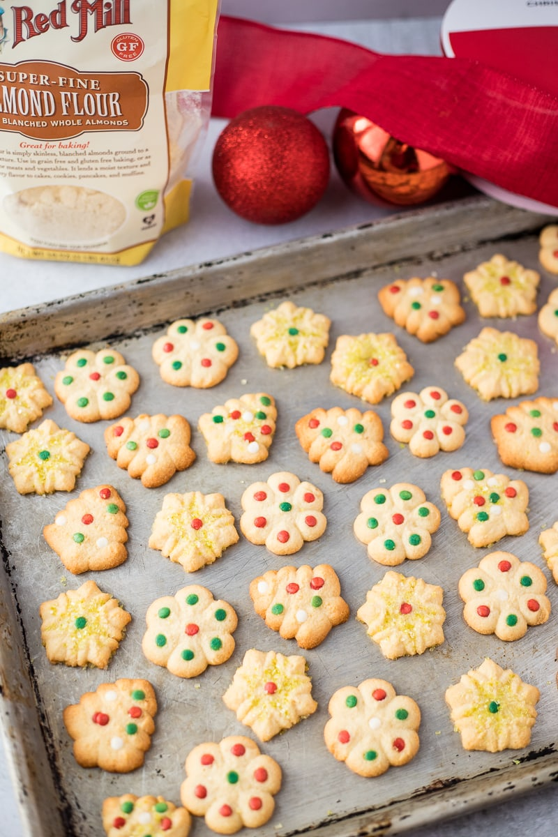 tray of decorated butter cookies in front of christmas tree balls and bag of almond flour