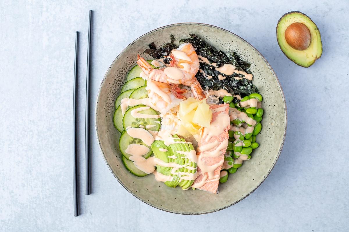 salmon sushi bowls next to black chopsticks and half of an avocado