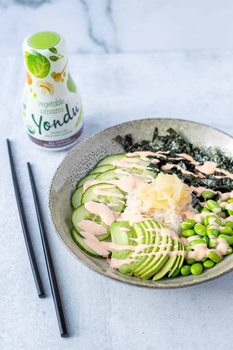 vegan sushi bowl with black chopsticks and bottle of yondu seasoning