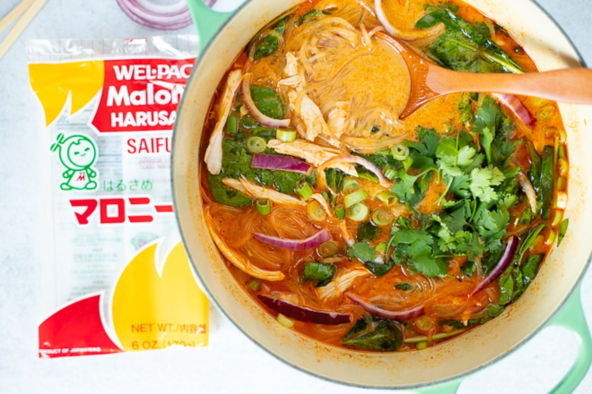 pot of red curry soup next to package of glass noodles